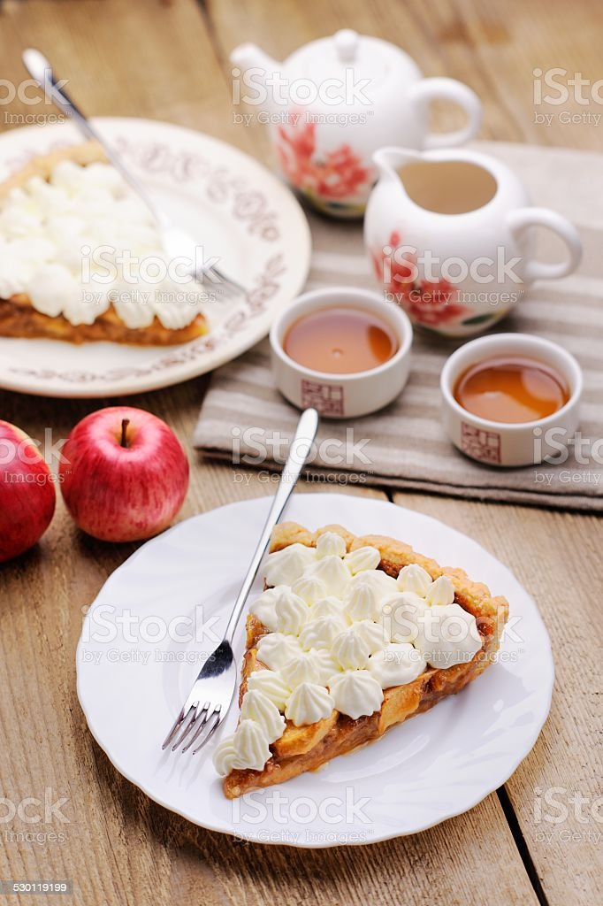Apple tart with whipped cream, red apples and teaware stock photo