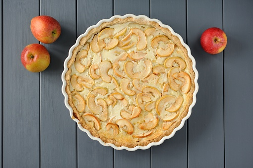 Apple tart with whole apples on grey stripped background
