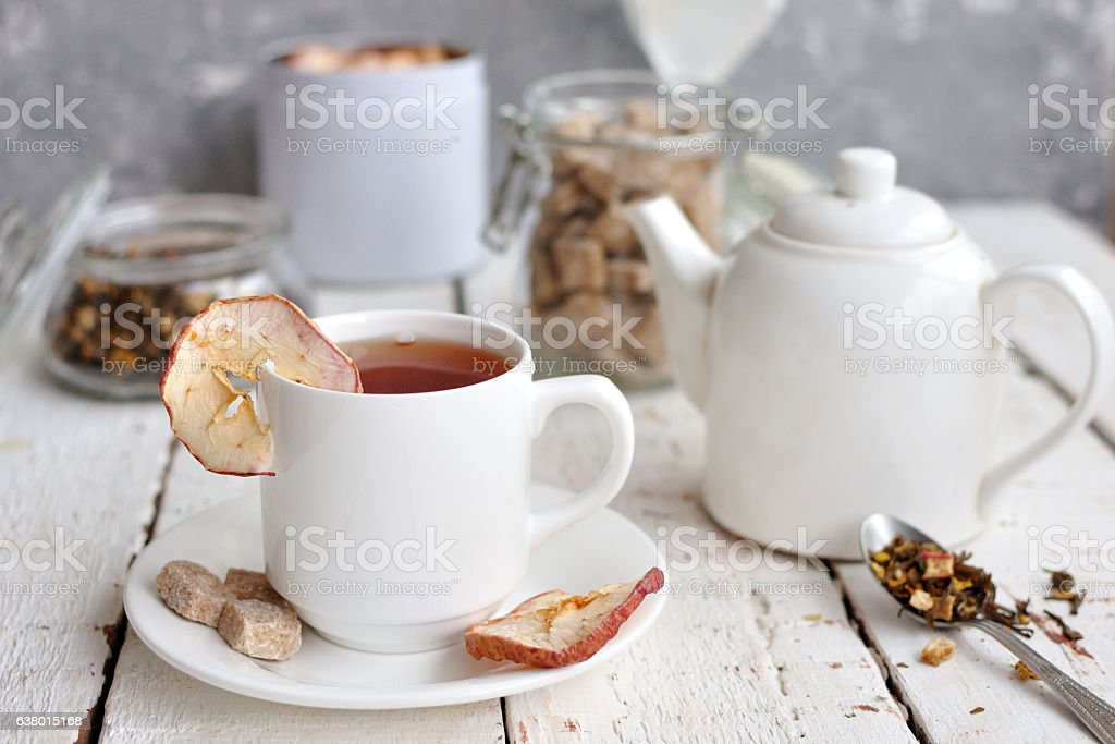 Apple tea served in white cup on white table. Selective focus stock photo