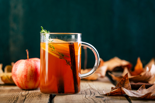 Apple tea with cinnamon, warming drink, old wooden background, fallen leaves