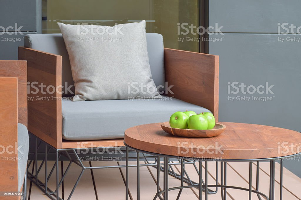 Apple tray on wooden top table next to outdoor cushion royalty-free stock photo