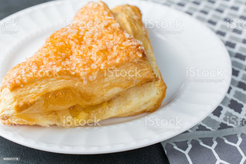 Apple turnover pastry on plate with gray napkin cloth stock photo