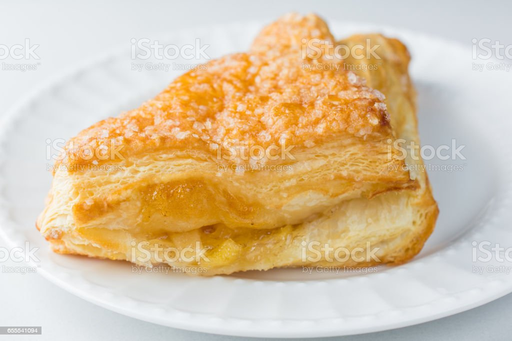 Apple turnover pastry on plate with white background close up stock photo