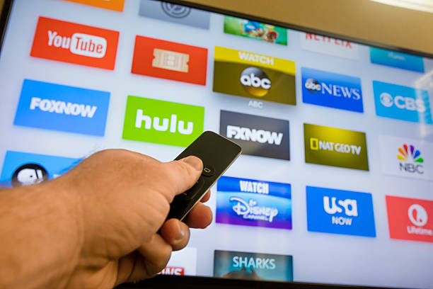 Apple TV - 4th Generation 2015 Las Vegas, USA - December 8, 2015: A young man browsing the selection of streaming TV options on the Apple TV. Apple TV is a device built by Apple Computers for streaming Television content and playing games.  netflix stock pictures, royalty-free photos & images