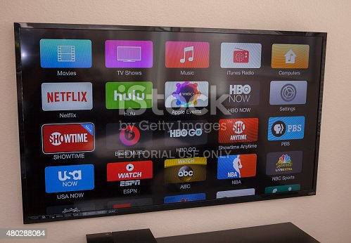 Las Vegas, USA - July 8, 2015: Apple TV being used on a flatscreen TV. Apple TV is a digital media player and a microconsole developed and sold by Apple Inc. It is a small network appliance and entertainment device that can receive digital data from a number of sources and stream it to a capable TV for playing on the TV screen.