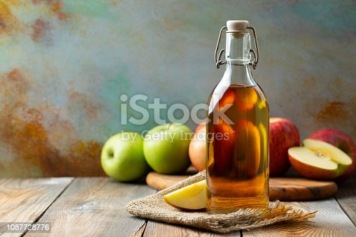 istock Apple vinegar. Bottle of apple organic vinegar or cider on wooden background. Healthy organic food. With copy space 1057728776