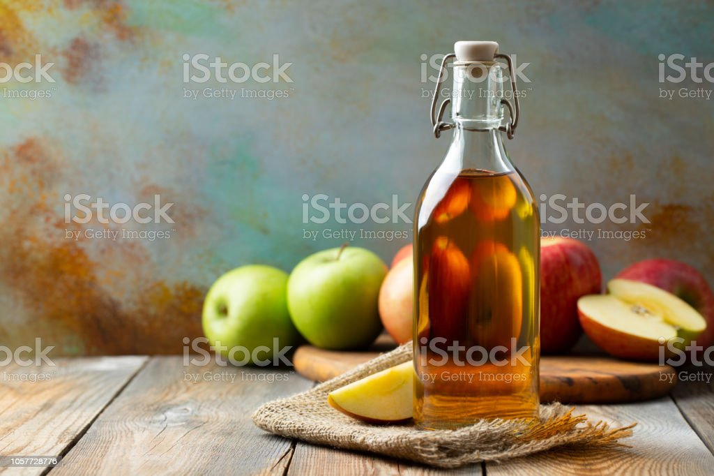 Apple vinegar. Bottle of apple organic vinegar or cider on wooden background. Healthy organic food. With copy space stock photo