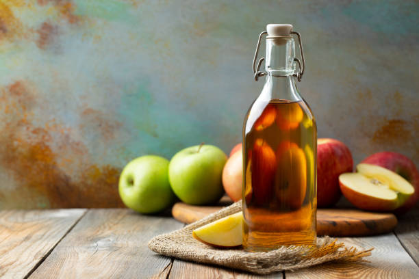 Apple vinegar. Bottle of apple organic vinegar or cider on wooden background. Healthy organic food. With copy space Apple vinegar. Bottle of apple organic vinegar or cider on wooden background. Healthy organic food. With copy space. apple cider vinegar stock pictures, royalty-free photos & images