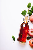 Apple vinegar in a bottle on white wooden table with apples and leaves. Rustic style. Top view, copy space.
