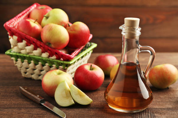 Apple vinegar in glass bottle on brown wooden table stock photo