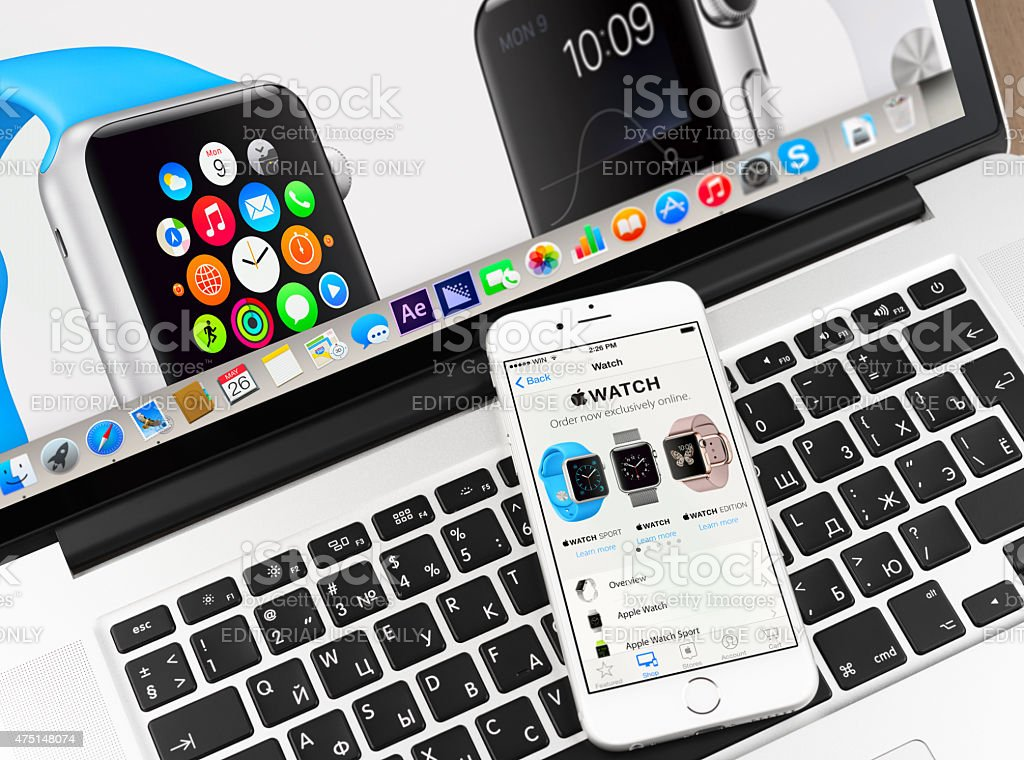 Apple watch on iPhone 6 and Macbook display stock photo