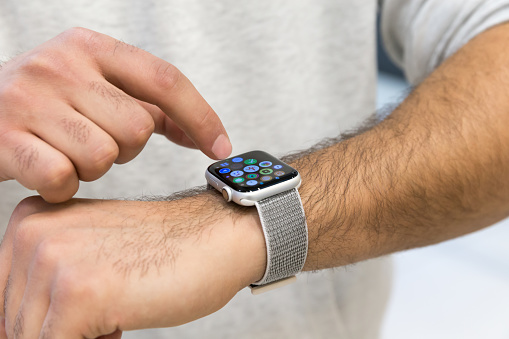 Apple watch shown on hand. Man's finger typing applications on the screen