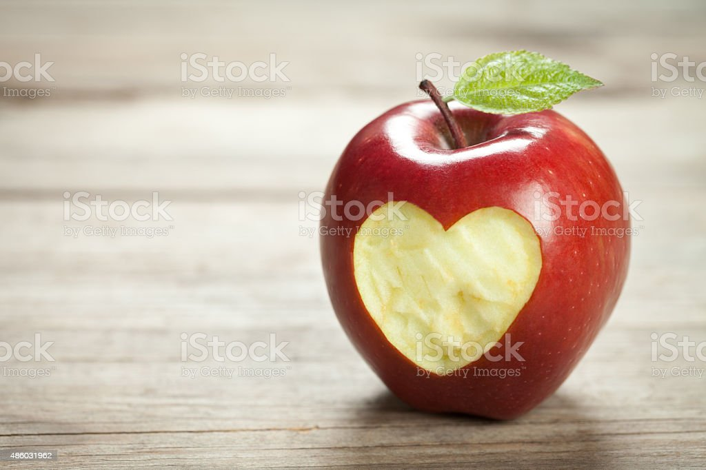 Apple with heart on old wooden table stock photo