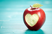 Apple with heart on turquoise table. On left side is empty space to put text or something else. This file is cleaned and retouched.