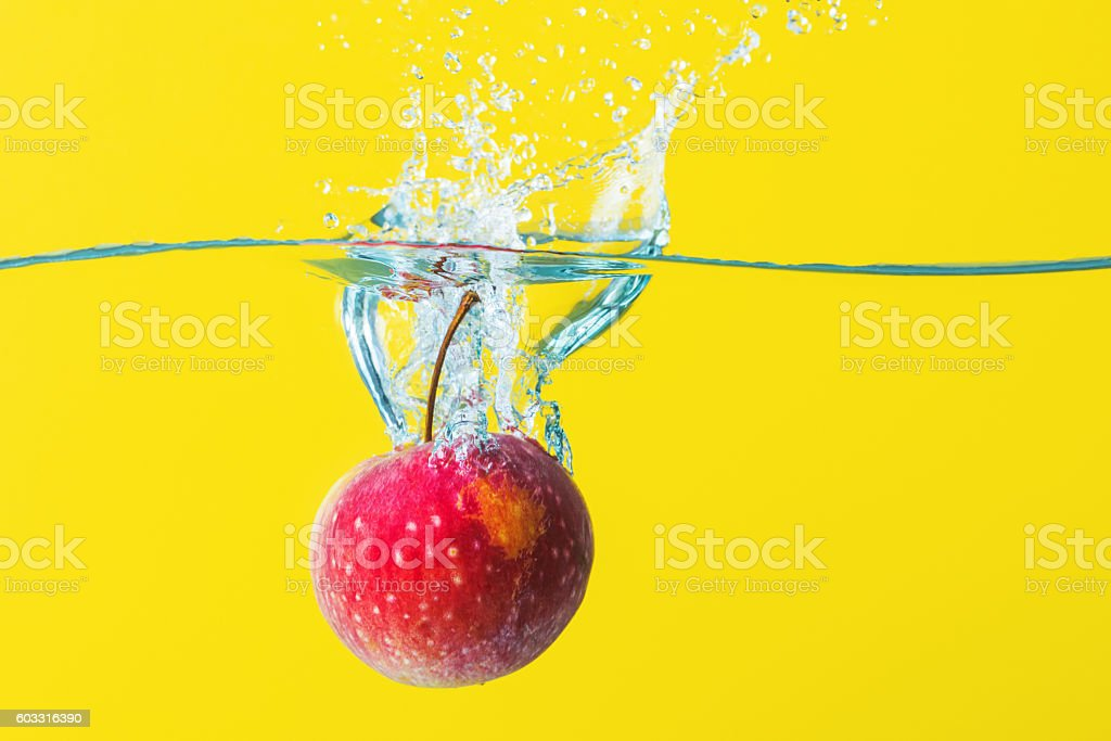 Apple with water splash on yellow background