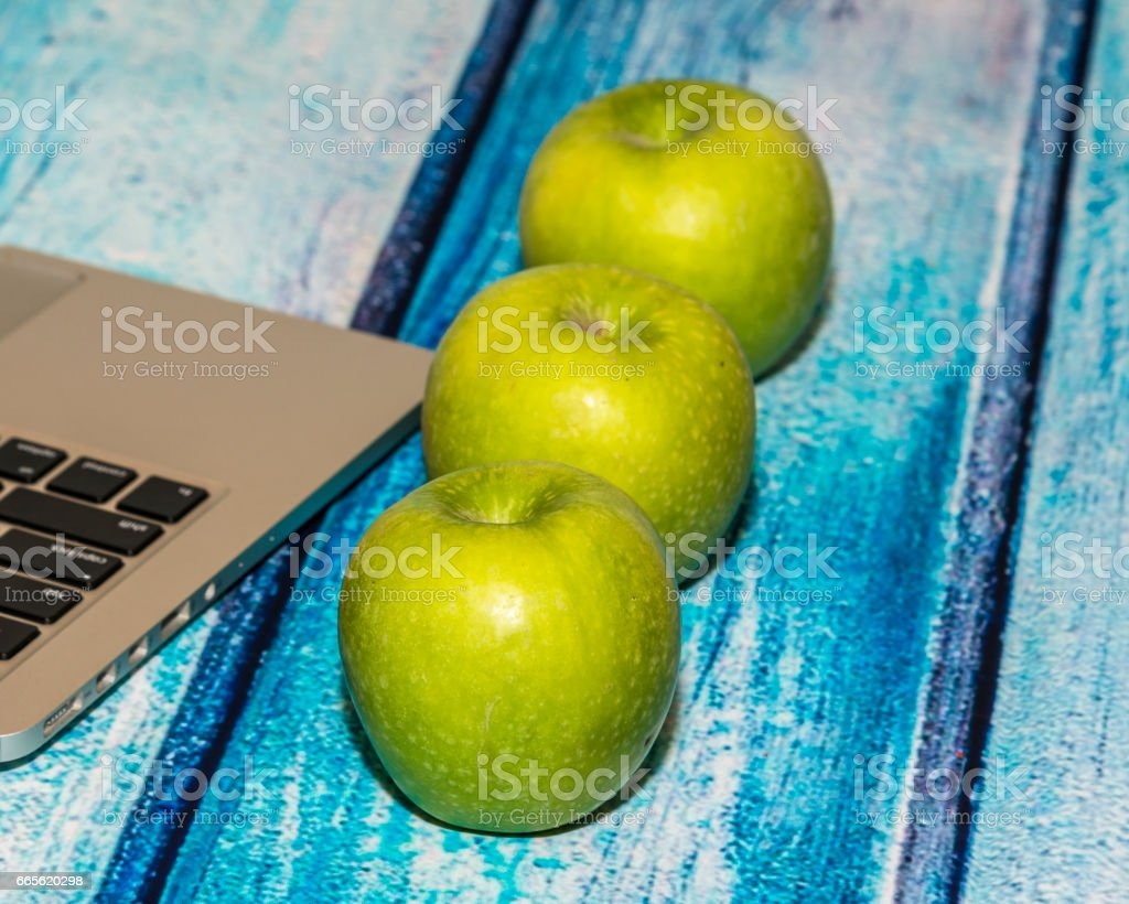 Apples and laptop on the blue wooden table stock photo