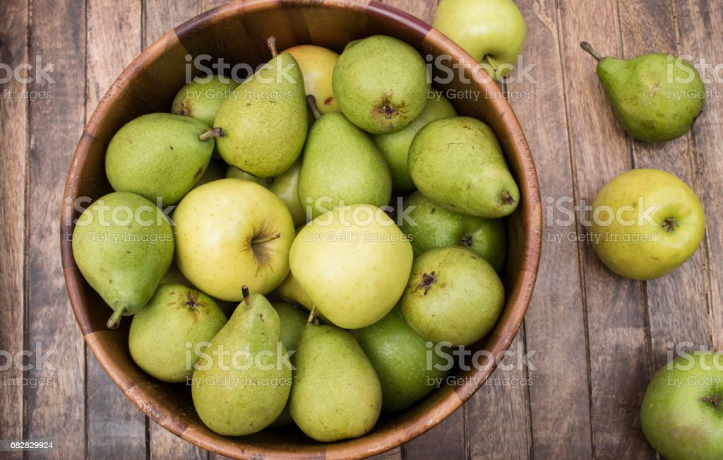 Apples and pears in wooden bowl stock photo
