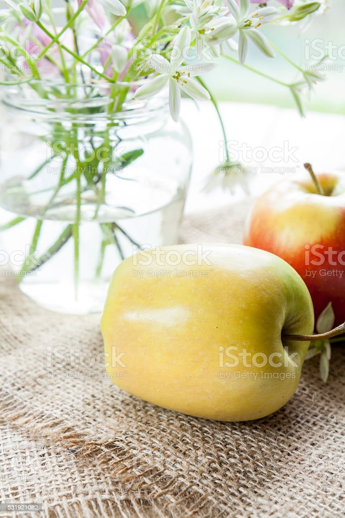 Apples and white flowers on table royalty-free stock photo