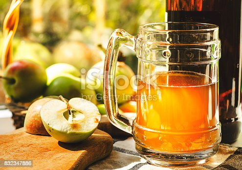 istock Apples, apple cider ale in beer glass and bottle on check pattern tablecloth. Rustic style 832347886