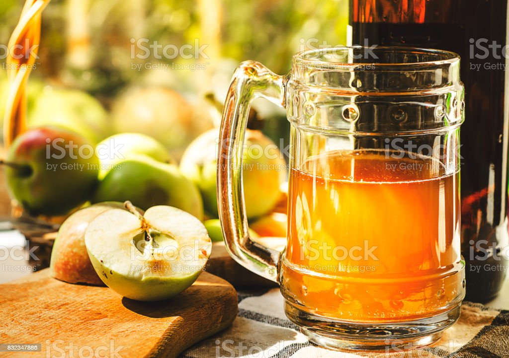 Apples, apple cider ale in beer glass and bottle on check pattern tablecloth. Rustic style stock photo