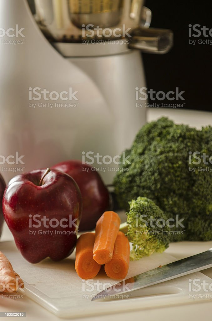 Apples Carrots and Broccoli in Front of Juicer royalty-free stock photo