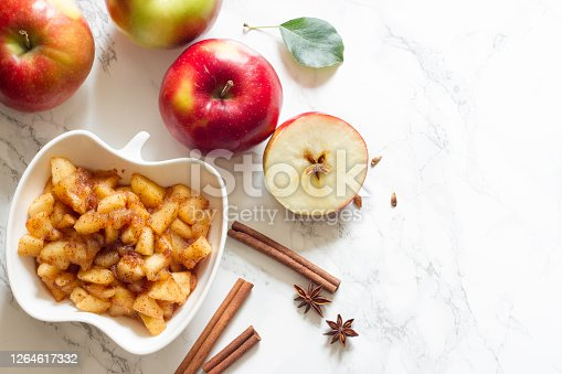 Apples, cinnamon and chunky applesauce on white background concept