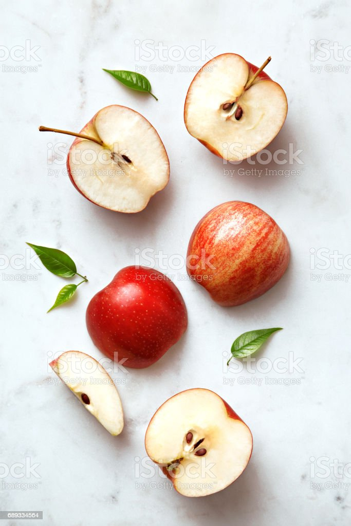 Apples flat lay on a marble background. Group of sliced and whole apple fruits viewed from above. Top view stock photo
