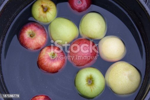 Red and Green Apples Floating in Bucket for Dunking