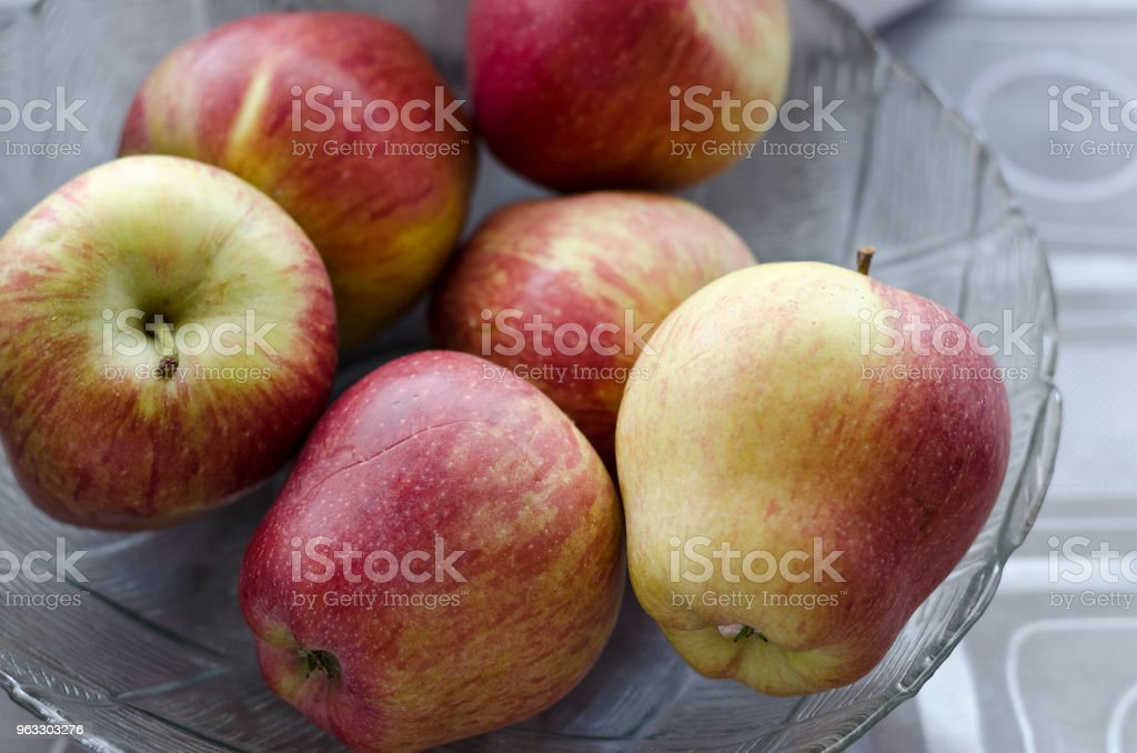 Apples in a glass plate on the table stock photo