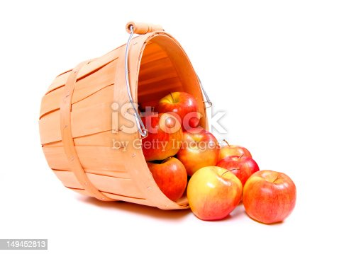 Apples spilling from a wooden harvest basket over white