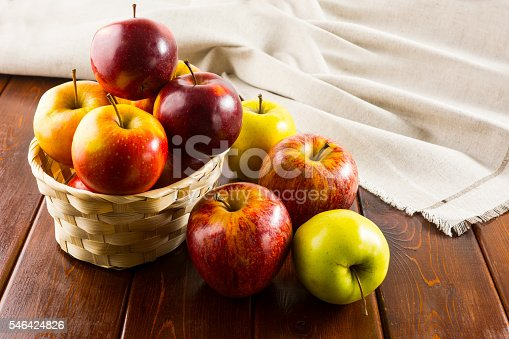 1020586746 istock photo Apples in the small wicker basket on dark wooden background 546424826