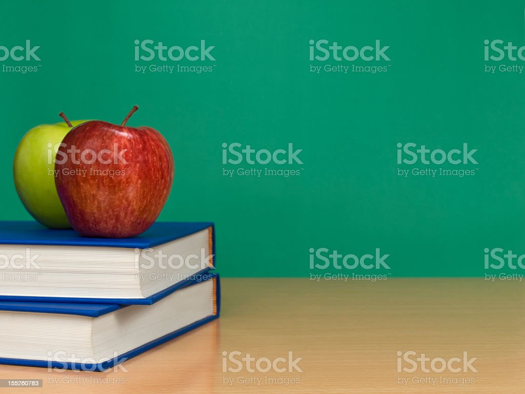 Apples on a stack of books on the table royalty-free stock photo