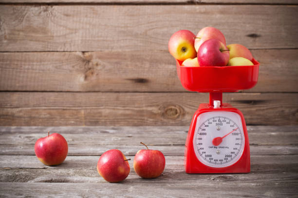 apples on red scales stock photo