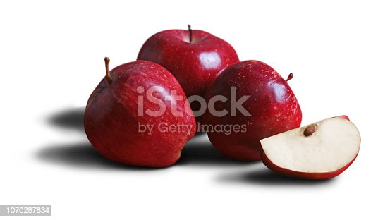 This is a color photograph of three whole apples and one sliced cross-section Apple isolated on a white background.