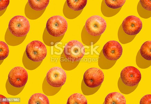 istock Apples on yellow background seamless 851927882