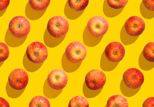 Cтоковое фото Apples on yellow background seamless