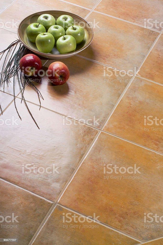 Apples over ceramic tiles stock photo