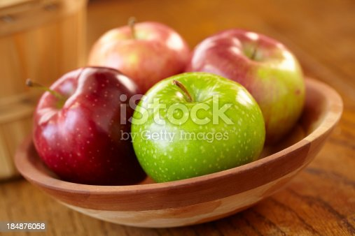 Wooden bowl of assorted apples shot with shallow focus on front apple.Please see some similar images from my portfolio: