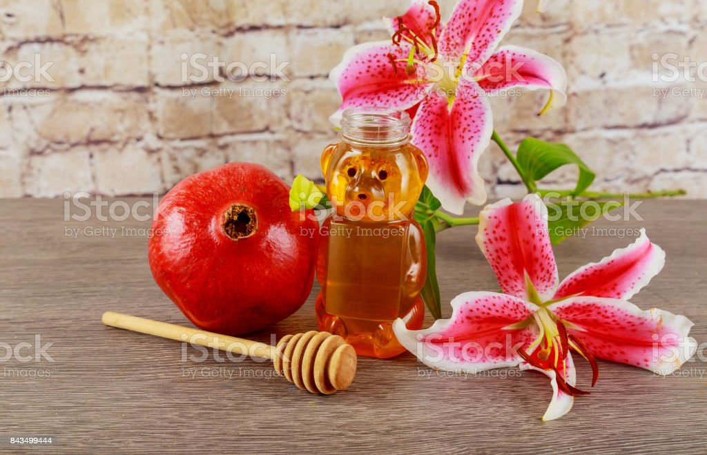 Apples, pomegranates and honey on a vintage dish in the kitchen. wooden table. The traditional setting for the Jewish New Year - Rosh Hashanah. stock photo