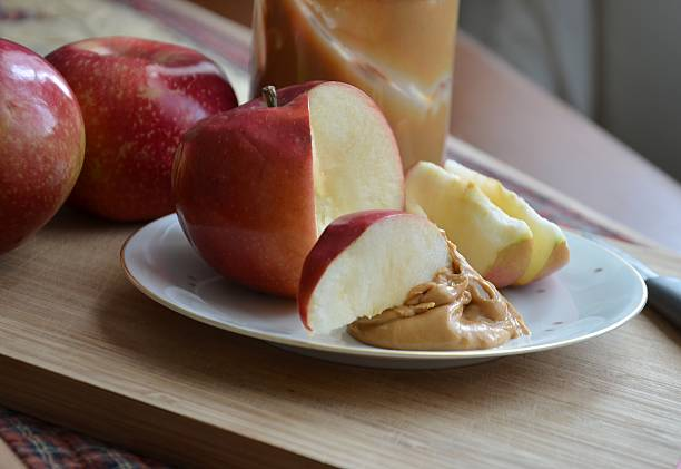 Apples Slices Dipped in Peanut Butter stock photo
