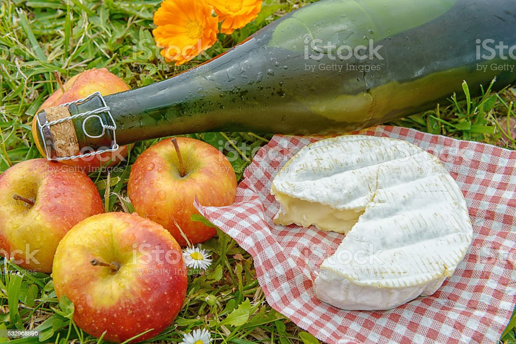 apples with cider and camembert in the grass stock photo