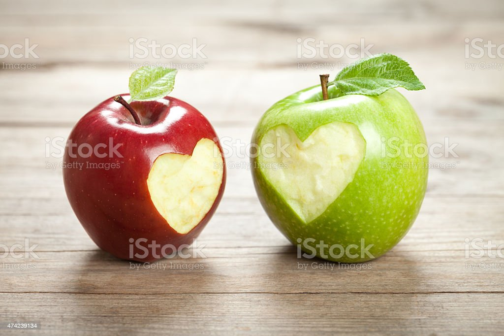 Apples with hearts on old wooden table stock photo