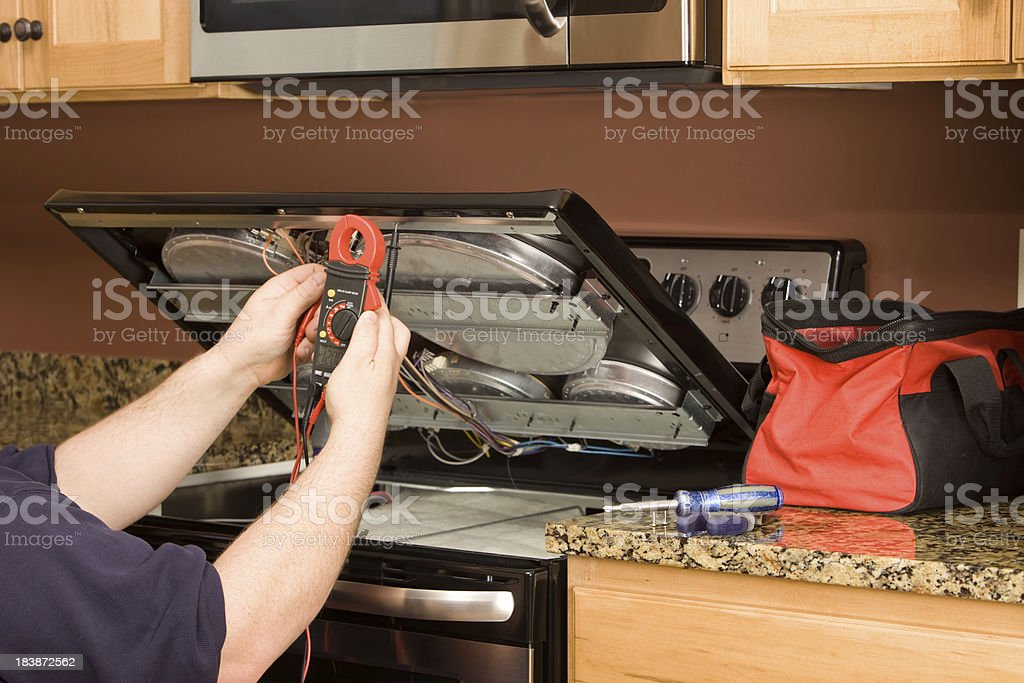 Appliance Repairman Using Multimeter on a Kitchen Range stock photo
