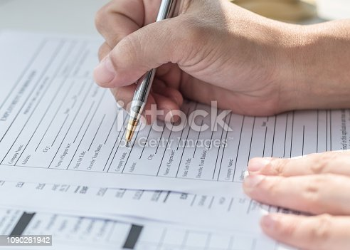 Applicant filling in company application form document applying for job, or registering claim for health insurance