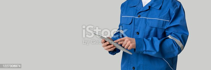 istock Application For Construction. Digital Tablet In Hands Of Unrecognizable Laborer In Uniform 1227308974