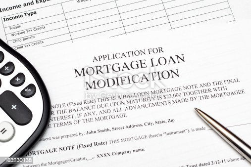 Application for mortgage loan modification with pen, calculator and income and expenses log.