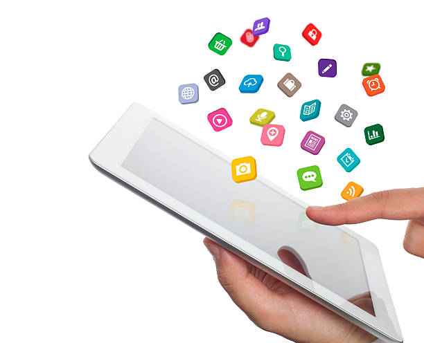 application icons fly off the tablet computer in hand stock photo
