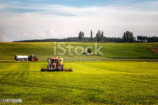 Application of manure on arable farmland with the heavy tractor who works at the field in Germany