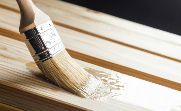 Auftragen des Lacks auf einer Holzoberfläche mit einem Pinsel – Foto
