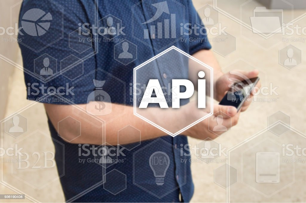 Application Programming Interface. API on the touch screen with a blur background of the businessman with the phone. The concept of application programming interface, API stock photo